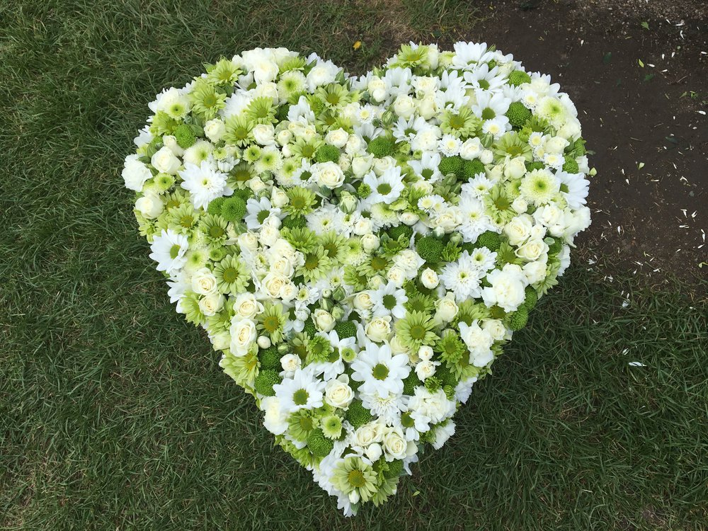 A large sized heart wreath with a pavé design with flowers layered over one another.