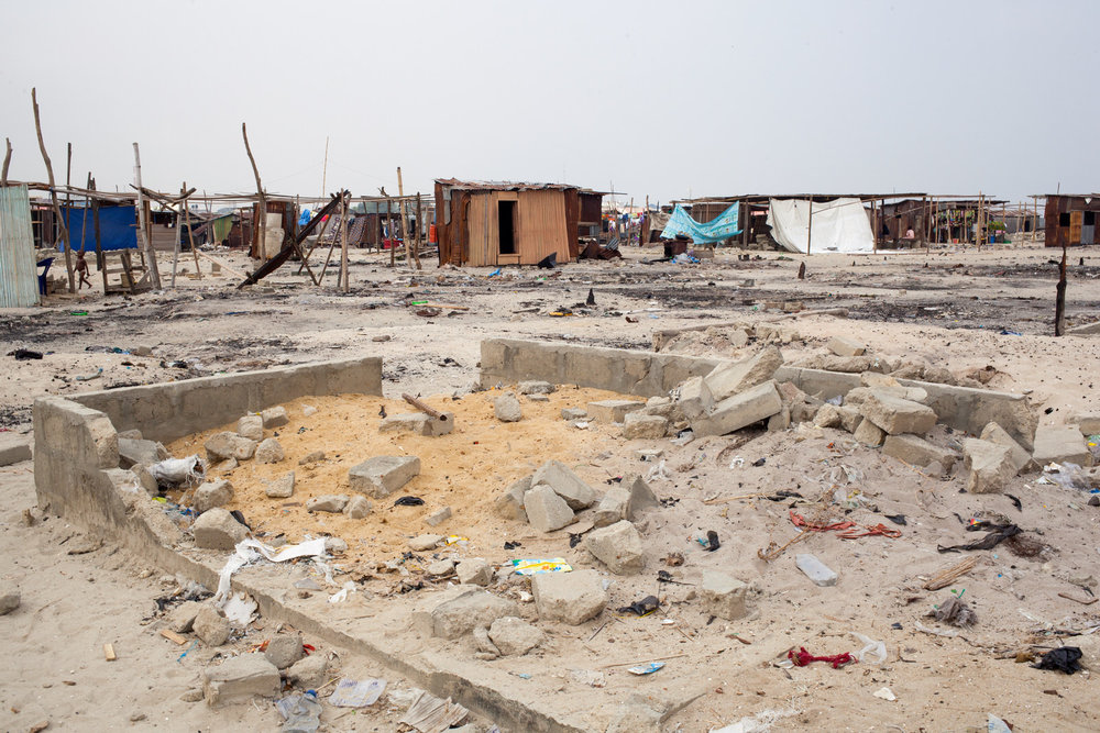 Remaining and new buildings sit amongst the rubble of homes razed by 'hoodlums' sent into the community.