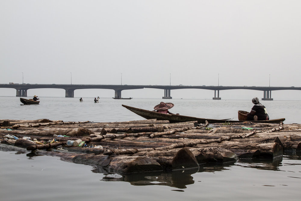 Fishing remains one of the main sources of livelihood for members of the community. Fishermen work in the lagoon with the Third Mainland Bridge in the background - the 2nd longest bridge in Africa.