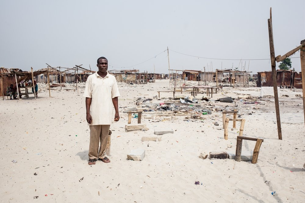Pascal Torshun, a fisherman and Otodo Gbame elder stands amongst the remnants of a church. Pascal sold drinking water, and is an active community member.