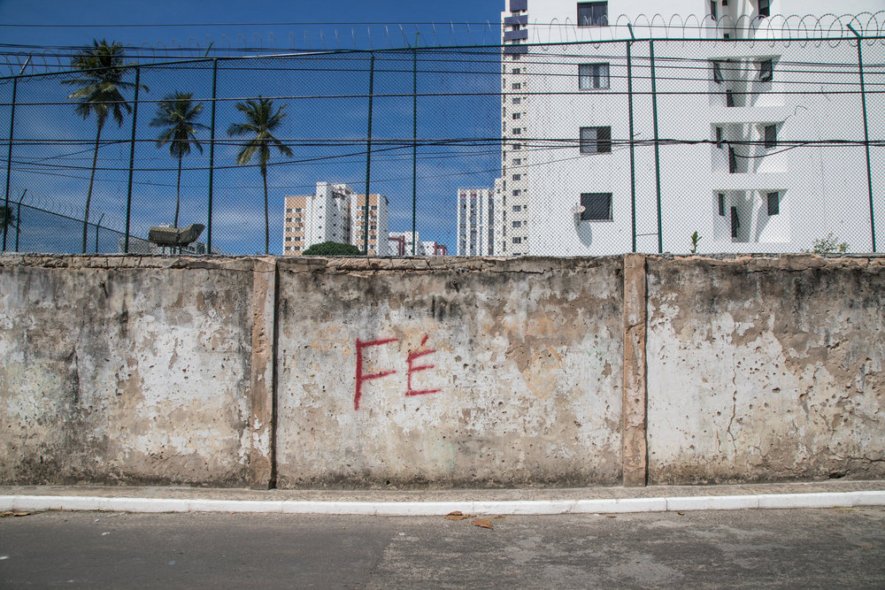The word 'Faith' is written on a wall on the Nordeste de Amarelina side of a wall that divides two communities of Salvador residents, the rich and the poor. The wall is a product of fear due to stigma and negative media representations.