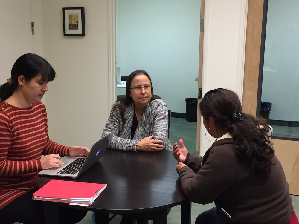 Clare Crawford (left) and Debbie Gish (middle), Spanish interpreter, meet with a client.