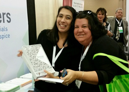 TAG Partners marketing specialist Erica Johnson (left) presents a custom-wrapped iPad Air to Stephanie Alexandro of Better Home Health Care Agency at the 2015 NAHC Annual Meeting.