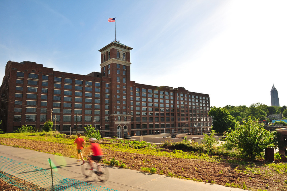View of Ponce City Market from the Atlanta BeltLine, with bicyclist and jogger in foreground