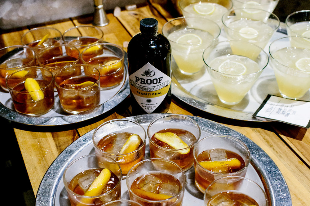 Trays of cocktails on a tabletop with a bottle of bitters in the center