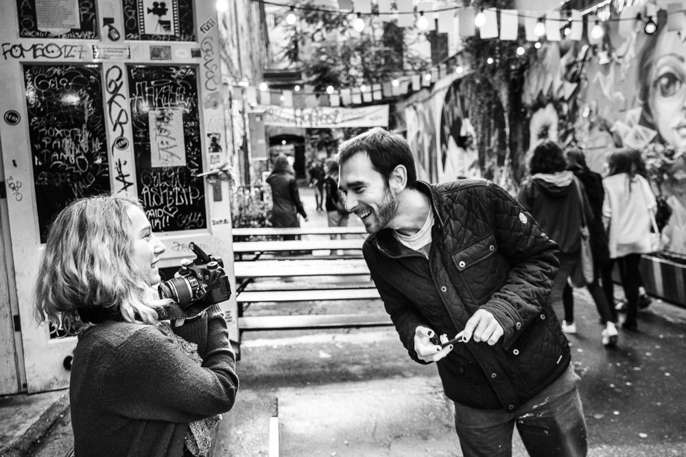 Nikki Marrone from  odefortheroad.com  shows Wesley Freeman Smith of  Colliding Lines  a photo she took in Dead Chicken Alley, Berlin.