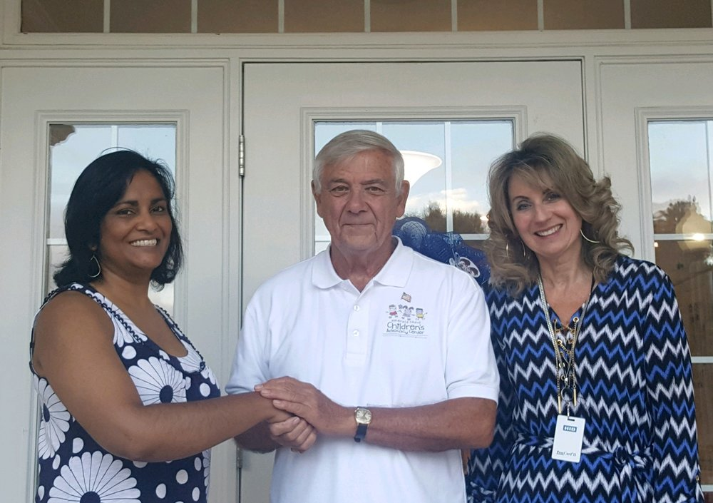 Dr. Lalitha Vadlamani-Simmers is welcomed as new Emerald Coast Children's Advocacy Center board member by president Bill Fletcher and CEO Julie Hurst.