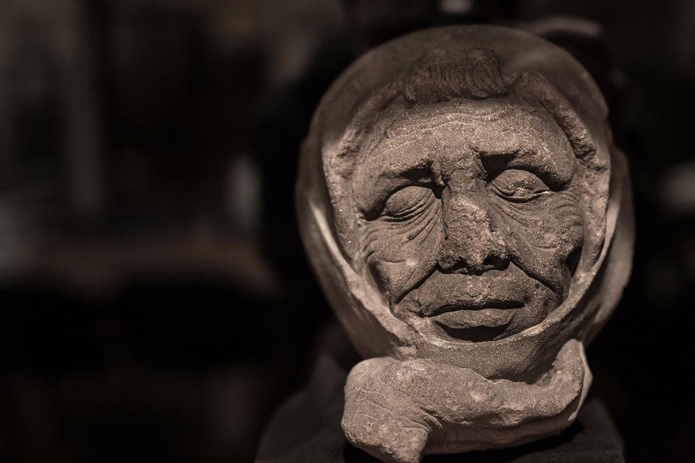 Bibliothèque Humaniste, salle de lecture :  la provenance de ce fragment est incertaine, mais cette tête d'homme aux yeux clos pourrait provenir d'un Saint-Sépulcre de l'église paroissiale Saint-Georges dans laquelle il est fait mention d'une telle composition monumentale, répandue dans le Rhin supérieur à partir du 14e siècle en 1530 et attribuée à Conrad Sifer qui y avait sculpté le jubé en 1489-1490.