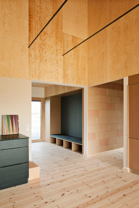 Bare plywood lines the walls and ceiling above the exposed clay blocks, and has been treated with a UV-protective sealant to preserve its colour.
