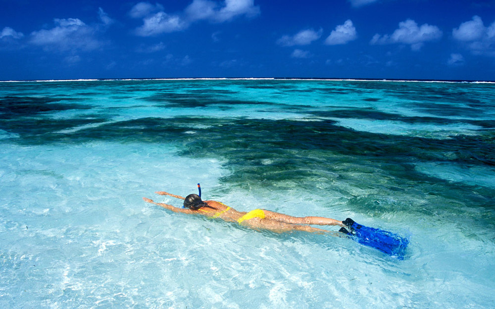 Lady snorkelling in a yellow bikini in clear waters in seychelles