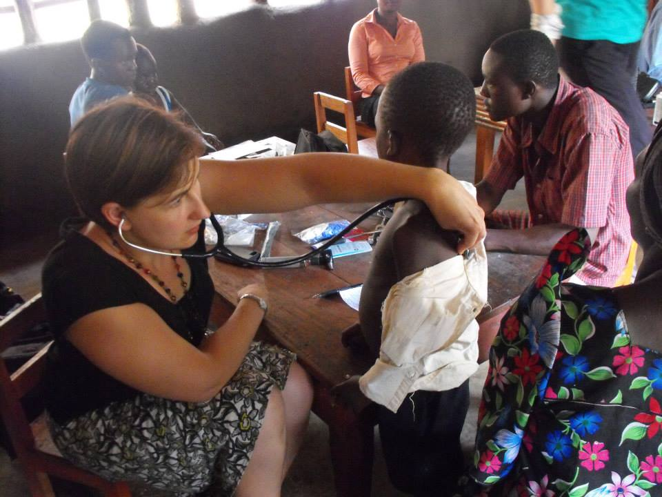 Dr. Laura examining a child on a health outreach clinic with PDI, 2013, Bududa (photo credit Lisa Umphrey)