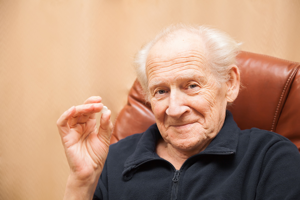 Elderly patient holding up pill