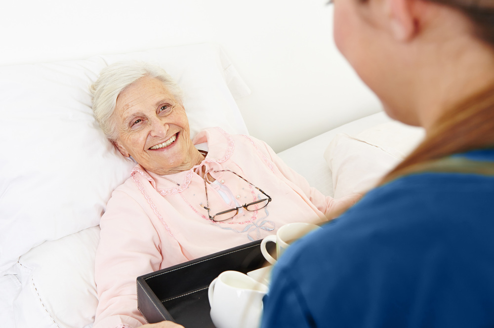 Assurance Home Care nurse with patient handing coffee tray