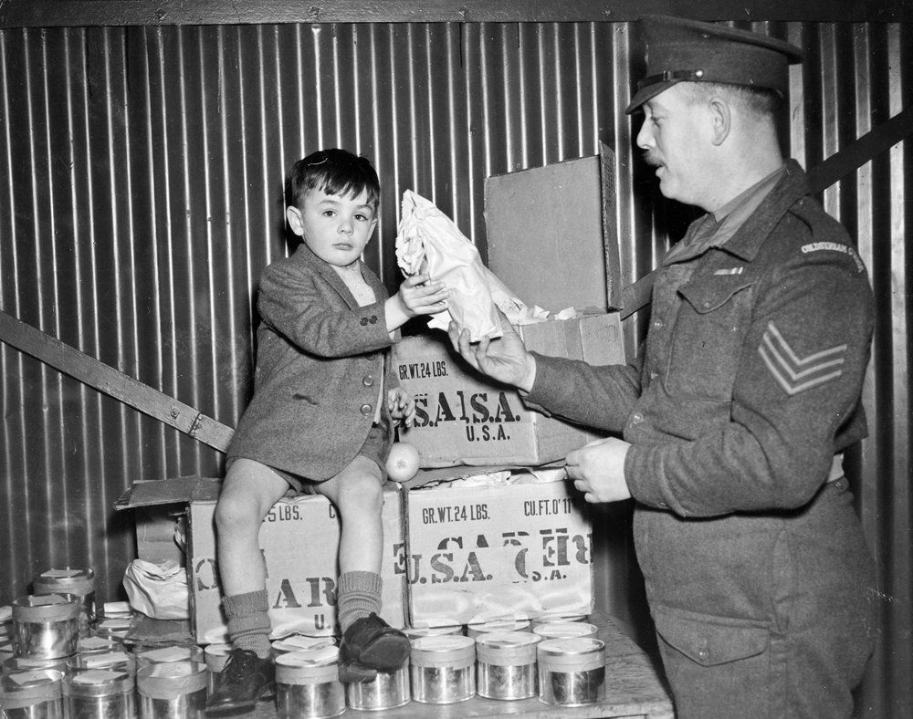 A member of the 2nd and Hq. Britian Coldstream Guards gave a Christmas party for the mothers and children of men stationed in Malaysia. Barry sits happily on boxes of gift food presented through CARE while Sgt. Wood, hands him a package to take home.