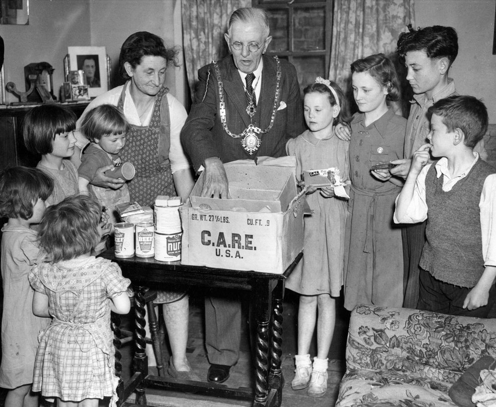 Mayor of Hertford, Hertfordshire, England, Mr. James Fredrick Keeble, delivers a CARE package donated by Mr. Allen Edward, Mayor of Hartford, CT, to war widow Mrs. Gladys E. Wilkinson and family.
