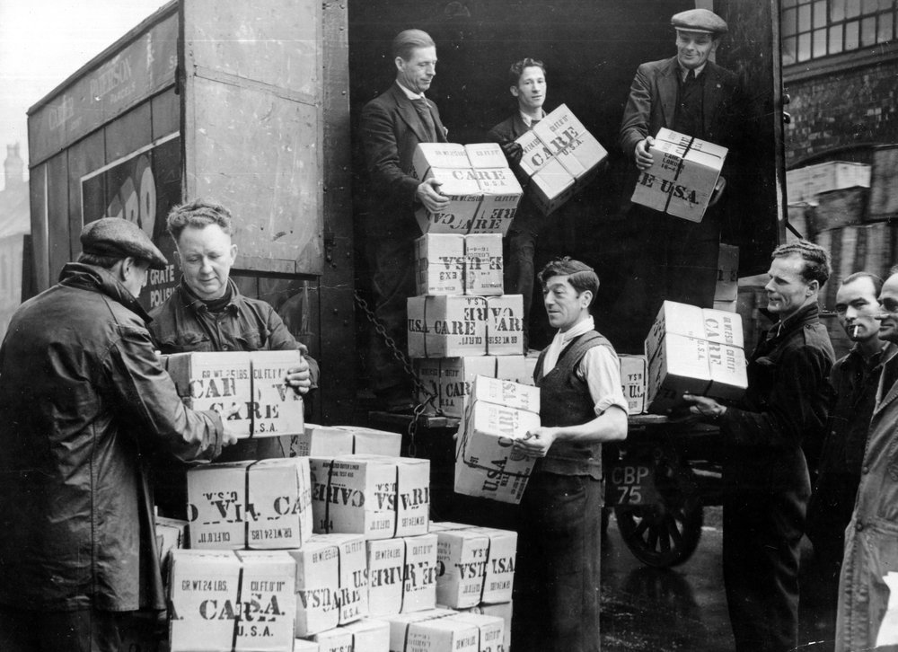 At the Timken Roller works in Birmingham, England, workers unload a recent shipment of 5200 CARE packages, sent as a gift to the plant employees from the Timken parent company in the United States. Many American firms send CARE packages to their employees in foreign branches, to help them supplement their meager rations.