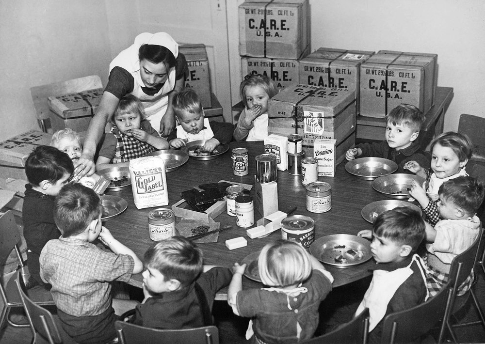 A nurse feeds Dutch orphans from CARE packages.