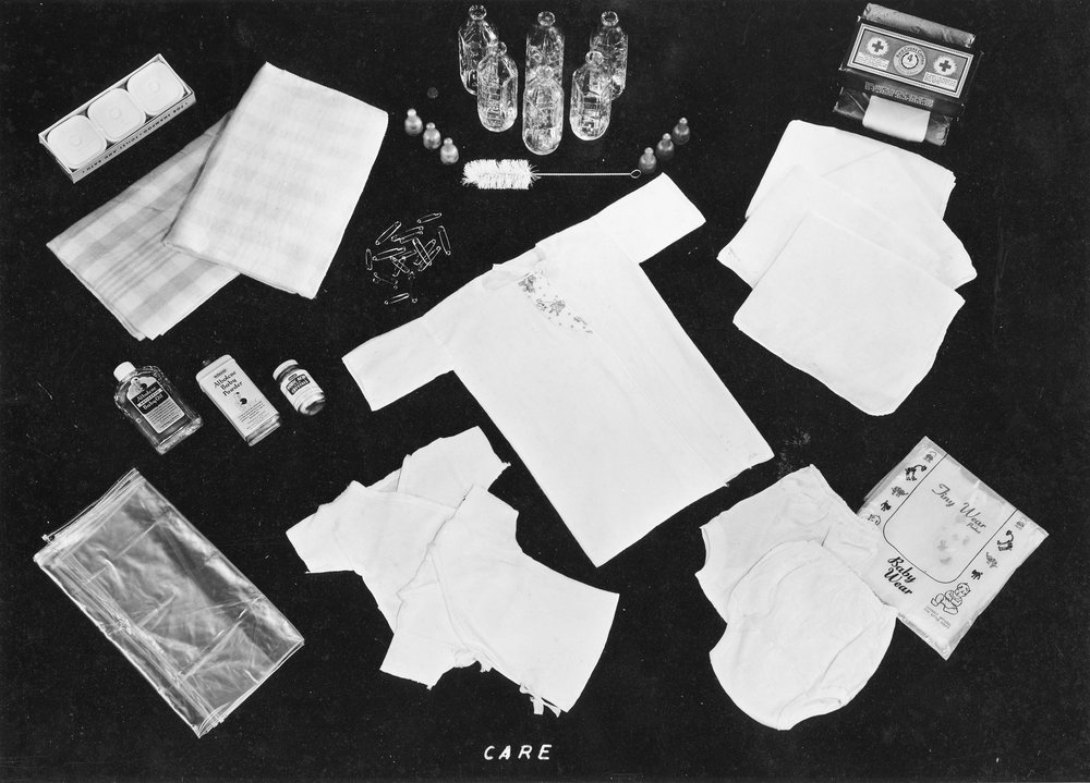 This photograph shows a CARE package specifically for an infant. it includes clothing, cleaning, and care supplies.