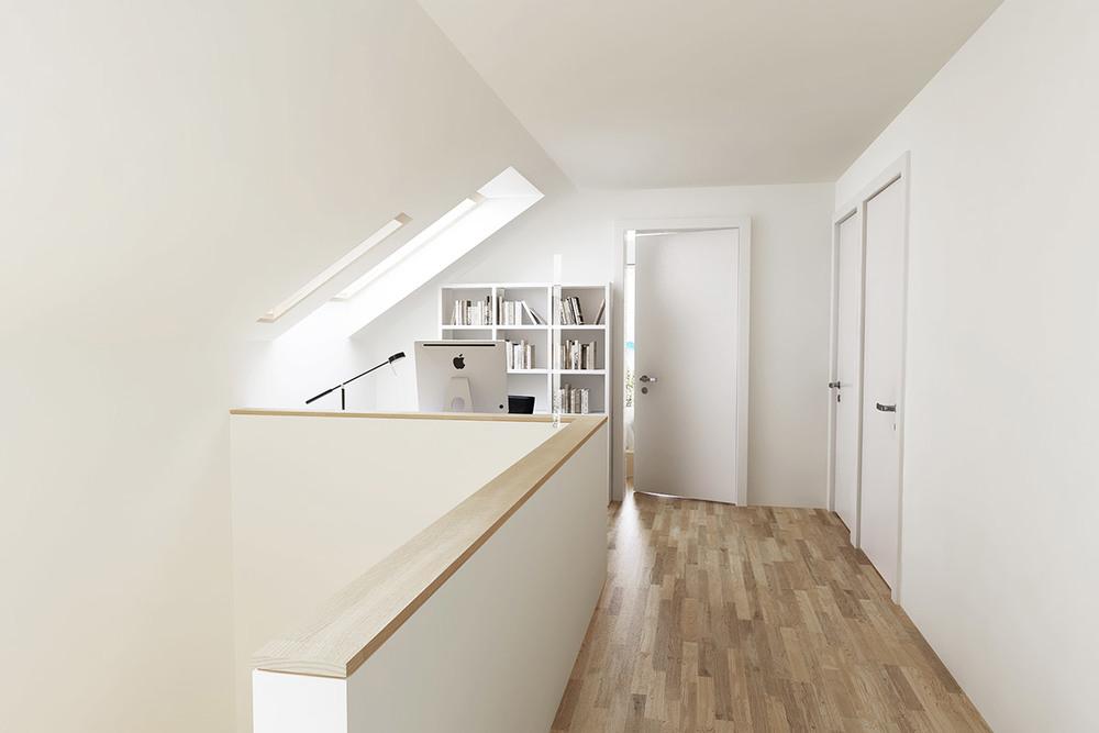 Stopnišče in dobro osvetljen hodnik v nadstropju z delovnim kotičkom.