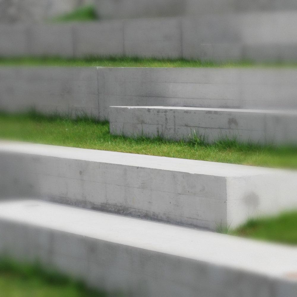 Detajl zidcev, položenih v travnato pobočje.