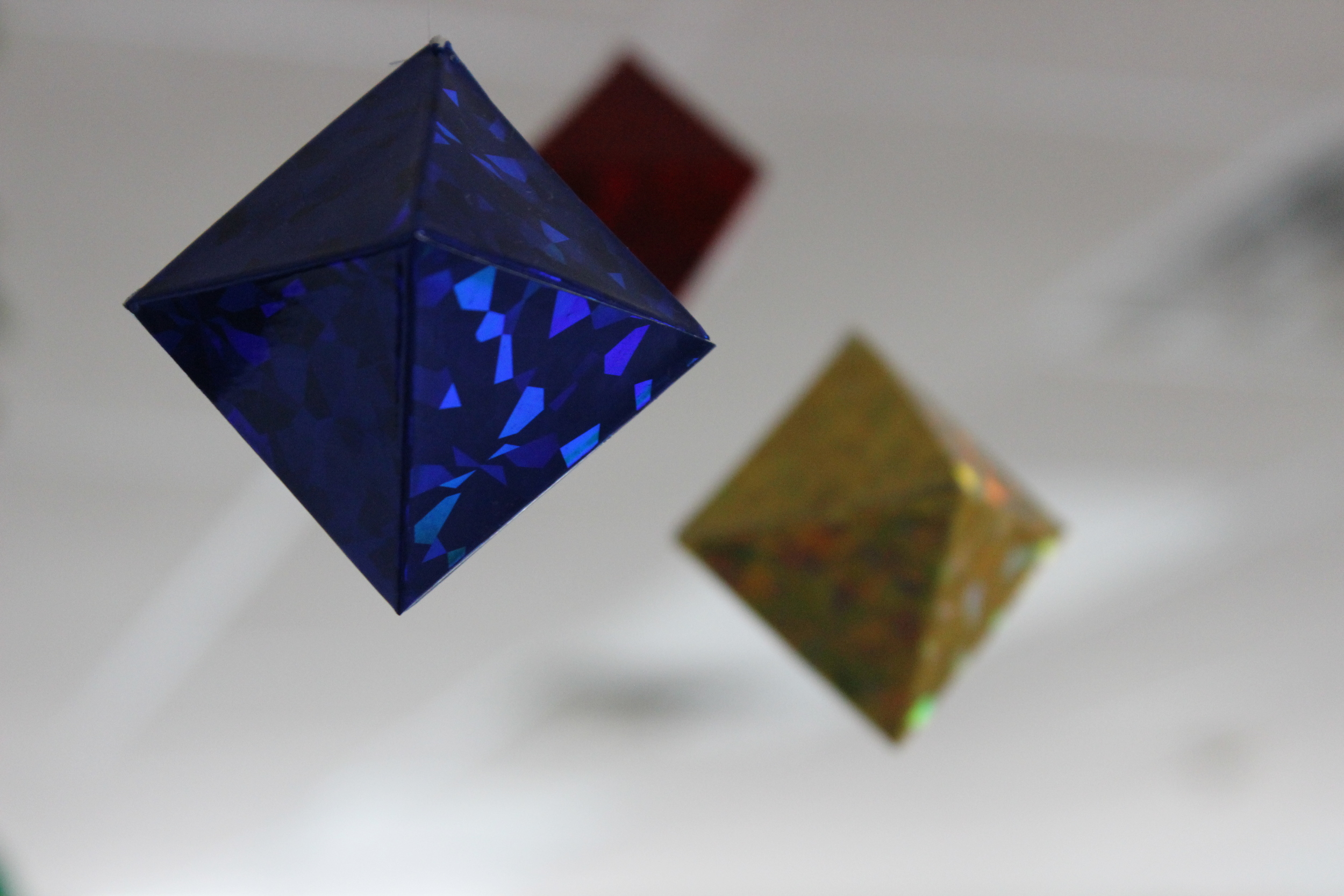 The Octahedron Mobile aids in the development of the visual sense, through visual focusing and tracking and is offered to the child around 2 months of age. At this time, the child is beginning to see color, so we offer primary colors in metallic paper, attracting the child to the contrasts of light and dark.