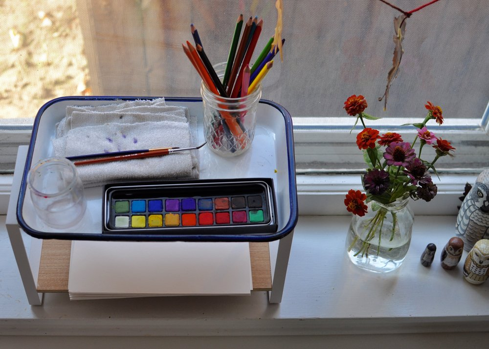 For a child who enjoys watercolors, a small shelving unit meant for use as a spice rack can double as windowsill storage for paint, brushes, cloths, a jar for water, watercolor pencils, and watercolor paper stacked below.