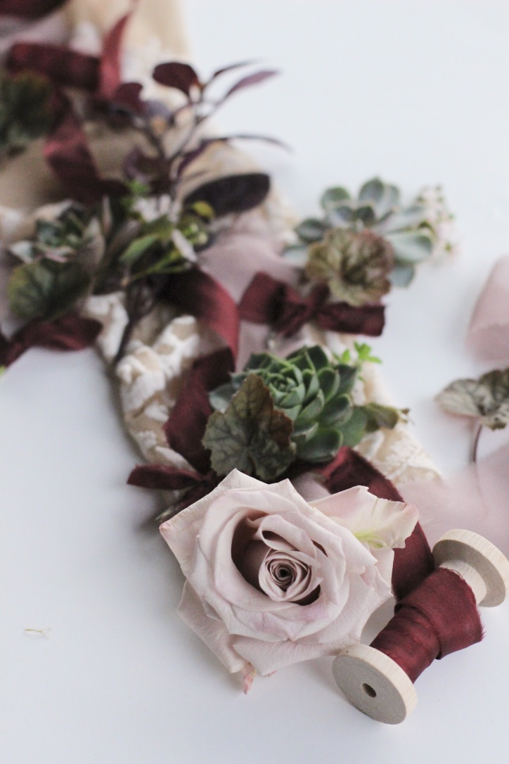 An Elegant Dark & Moody Toned Wedding | Black, Oxblood, Burgundy, Purple Theme with Artichoke, Winter, Fall, Outdoor Wedding | Hand Dyed Silk Ribbon | Detail Flatlay | Succulent Boutonniere |  Florals by Loveshyla.com