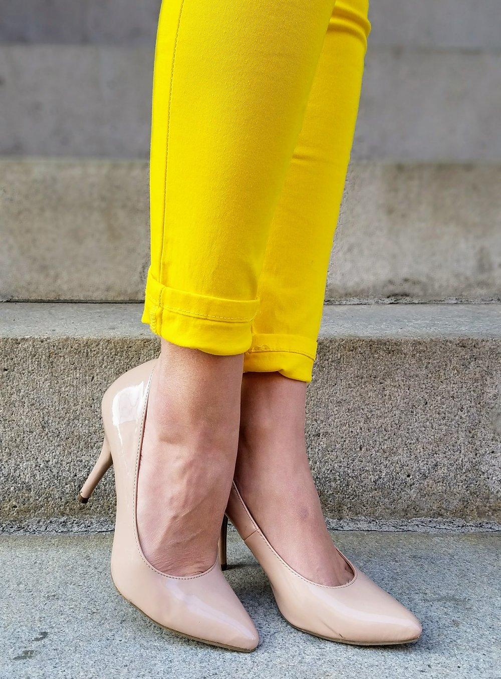 Nude heels and yellow jeans closeup for a blog.