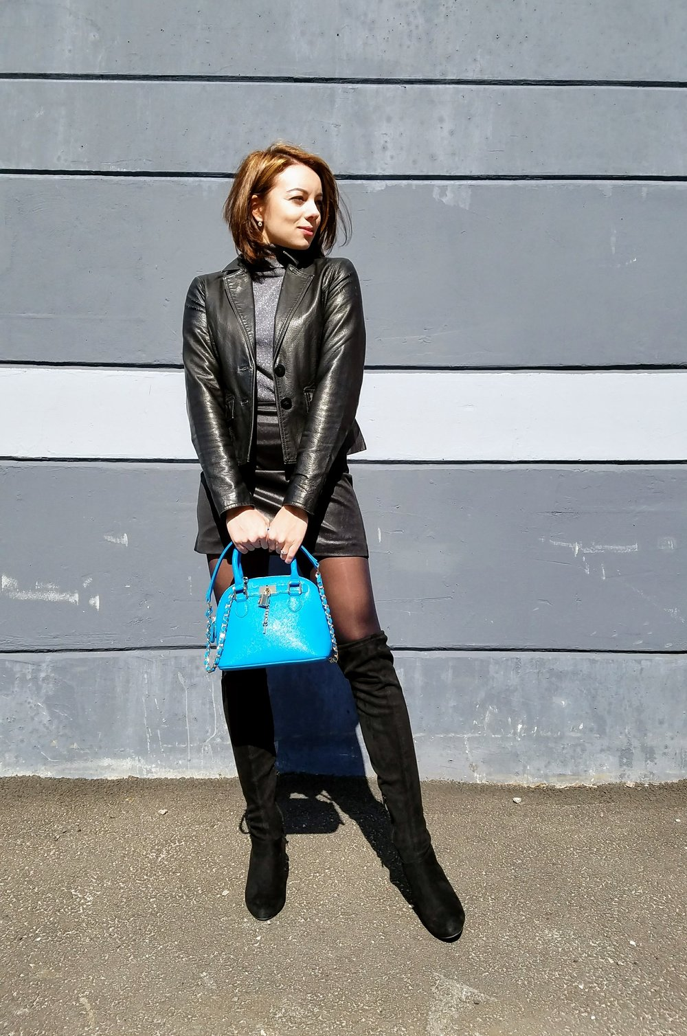 Black leather outfit, blue purse in front of gray wall.
