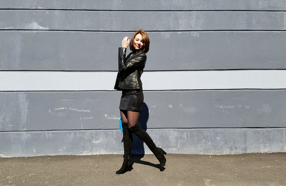 Black leather jacket and skirt, thigh high boots, blue purse, gray wall.