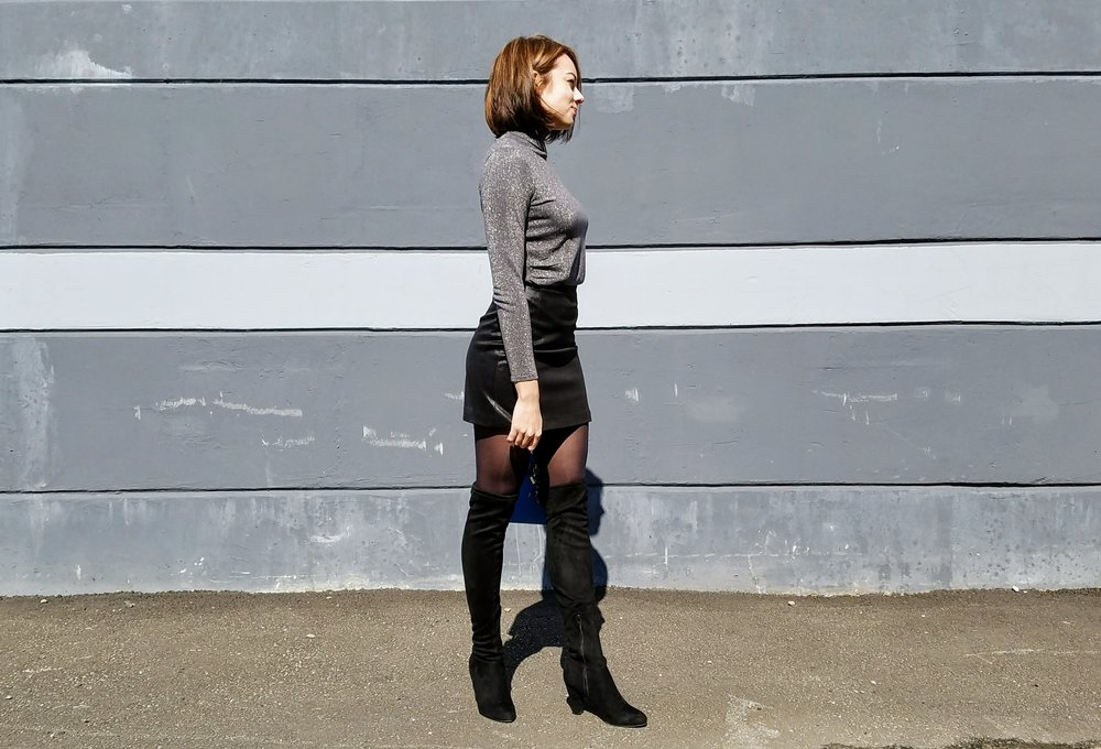 Gray turtleneck, black leather skirt, black thigh high boots, highlights and short bob.