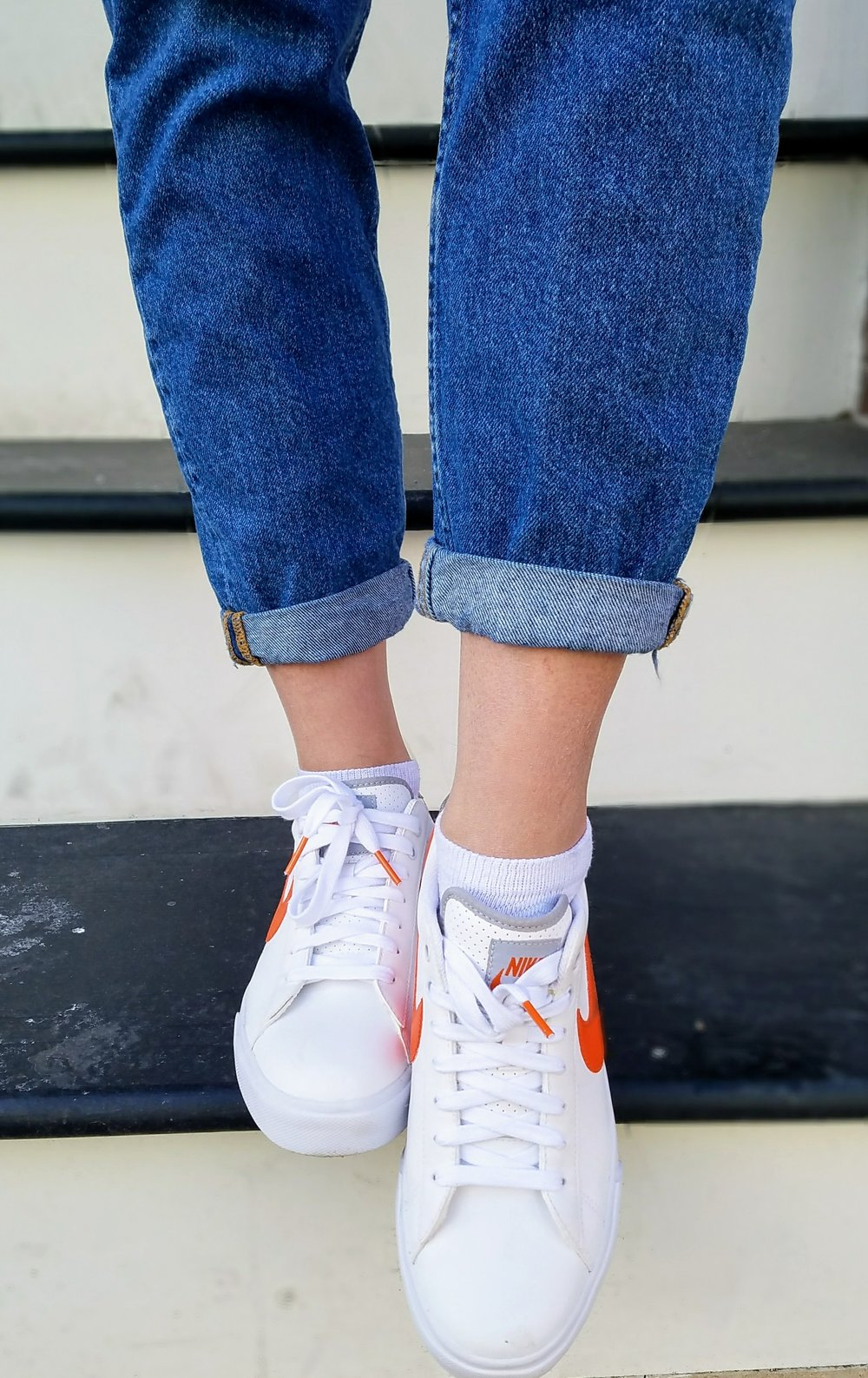 Close-up of mom jeans and white Nike sneakers