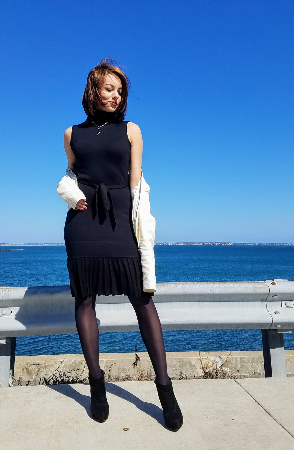Black turtleneck dress, black ankle boots, white leather jacket.
