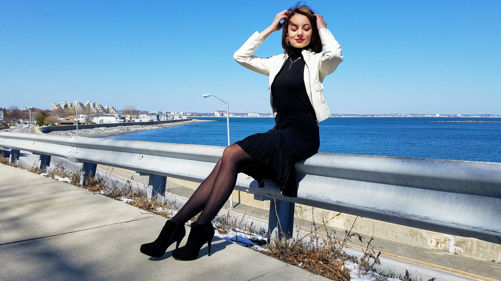 A girl posing in front of the beach and wearing a black turtleneck dress, black ankle boots, and a white leather jacket.