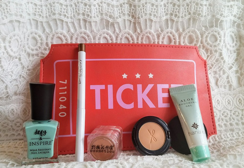 A photo of Ipsy glam bag and five beauty products, which are nail polish, eye-shadow, soothing gel, eyeliner, and bronzer.