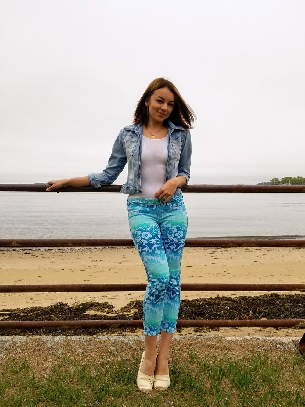 A girl standing by the beach wearing a white t-shirt, jean jacket, colorful pants with blue and green pattern.