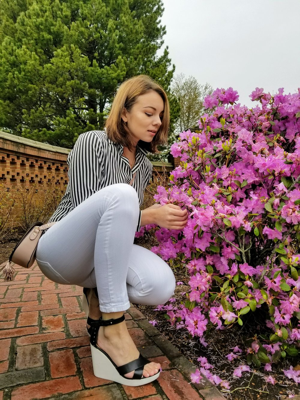 A girl sitting by the pink flowers, wearing white jeans, blouse with stripes, and black and white wedges.