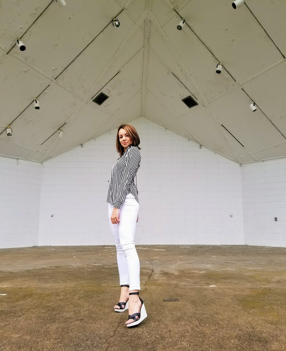 A blogger posing under a big white roof, wearing black and white outfit.