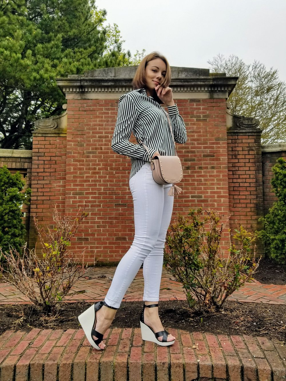 A blogger posing in the garden, wearing white jeans, black and white wedges, and a blouse with black and white stripes.