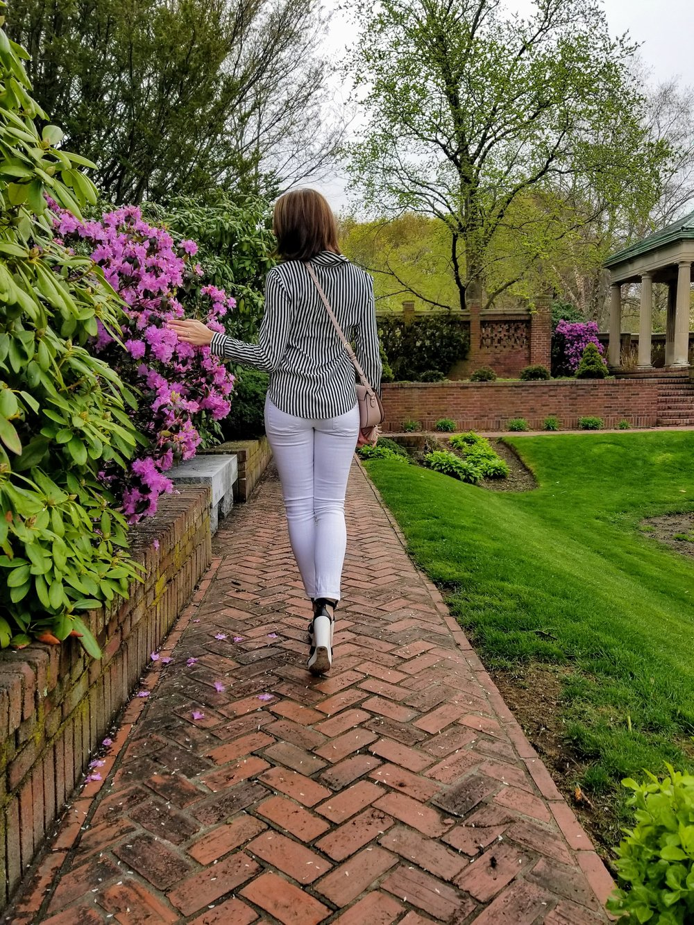 A photo of a girl walking away towards pink flowers on the tree, wearing white jeans, black and white wedges, and a blouse with black and white stripes, and a pink bag.