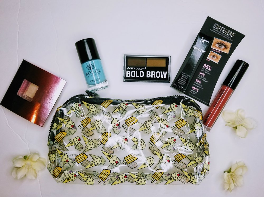 A photo showing a little glam bag, and five makeup and nail products, which are a highlighter, lipstick, mascara, nail polish, and brow powders.