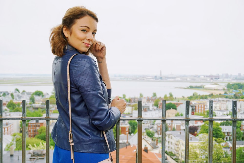 A photo of a girl swearing a blue leather jacket. Boston's view in the back.