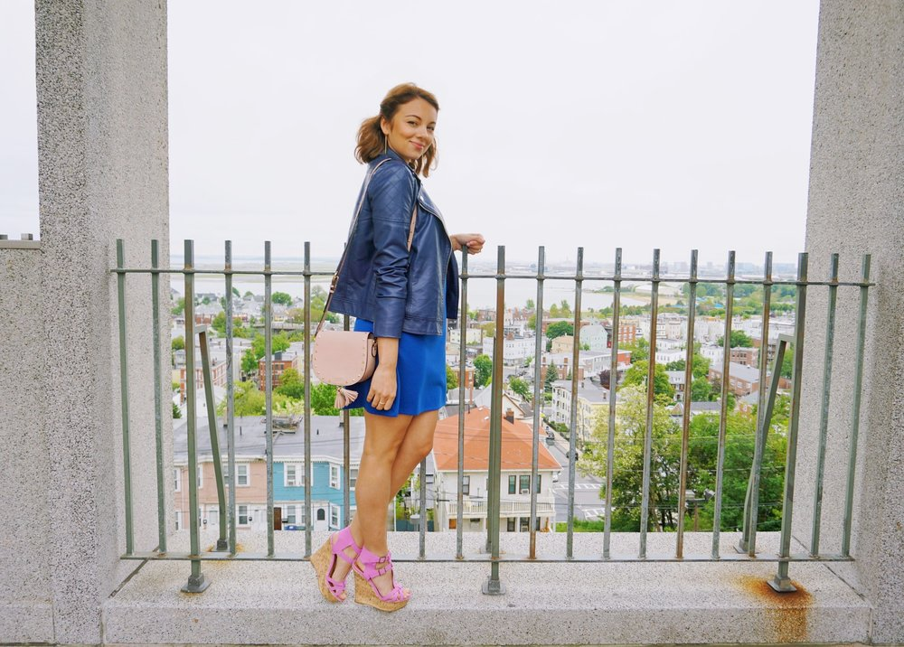 Beautiful Boston view behind a blogger who is wearing blue dress and blue leather jacket,t, lavender wedges, and pink bag.