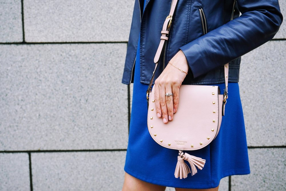 Details of blogger's outfit: blue dress, blue leather jacket, and pink bag..