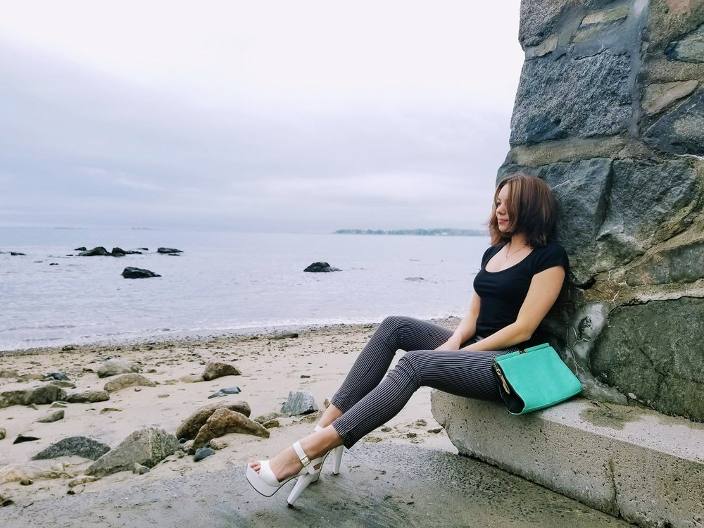 A blogger sitting by the beach, wearing stripped pants, black t-shirt, white heels, and green bag.