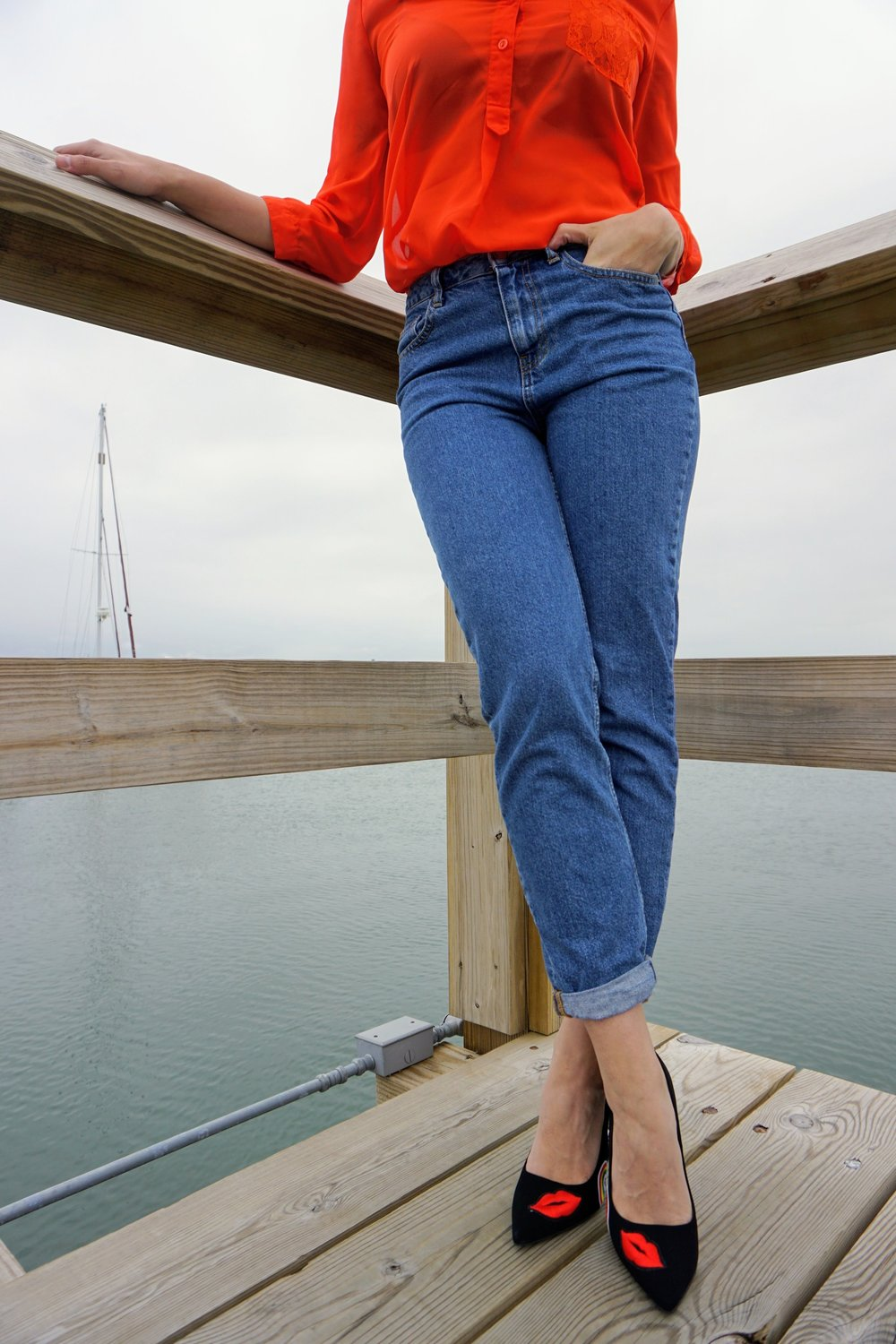 An outfit closeup on a blogger: blue mom jeans, a bright orange blouse, and black heels with two hearts on them.