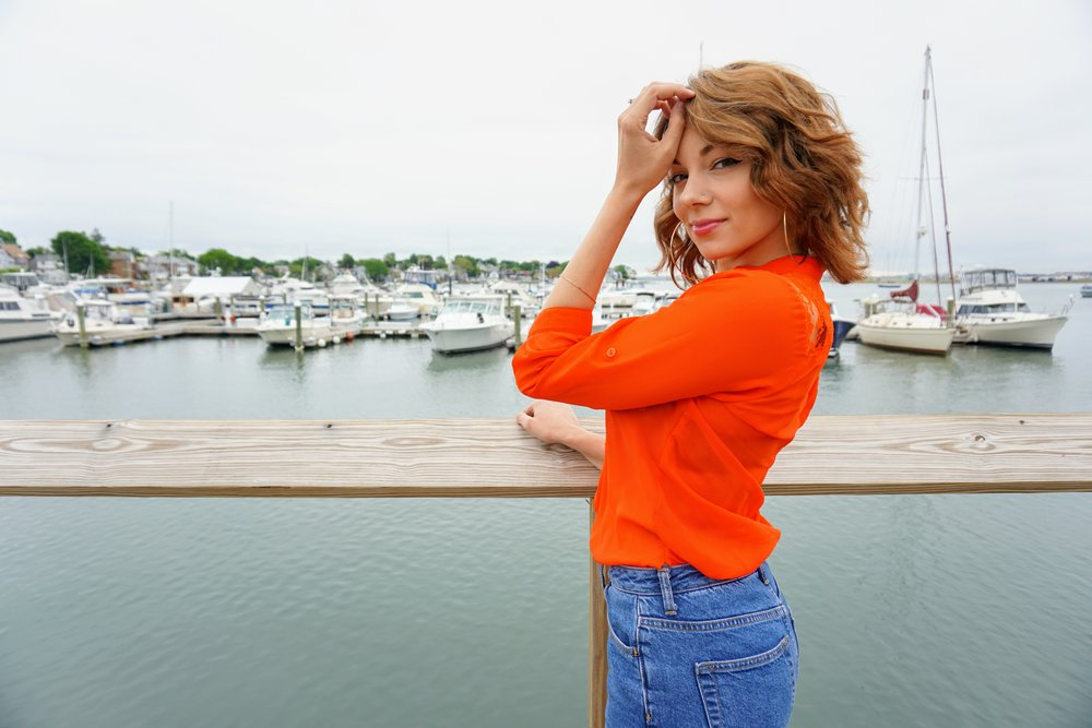 A fashion blogger posing near the water, wearing bright orange blouse and blue jeans.