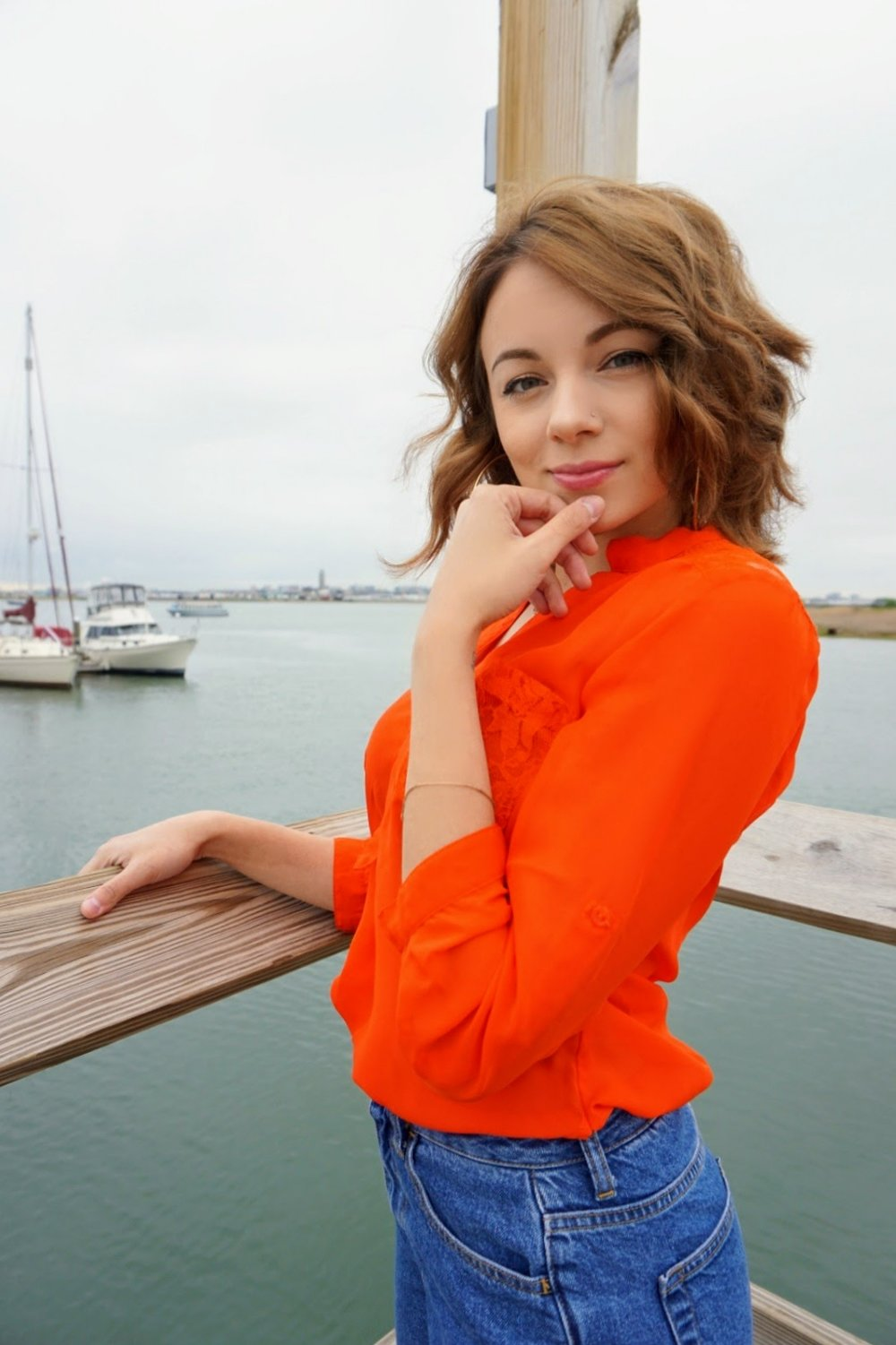 A blogger facing you, wearing a bright orange blouse and mom jeans.