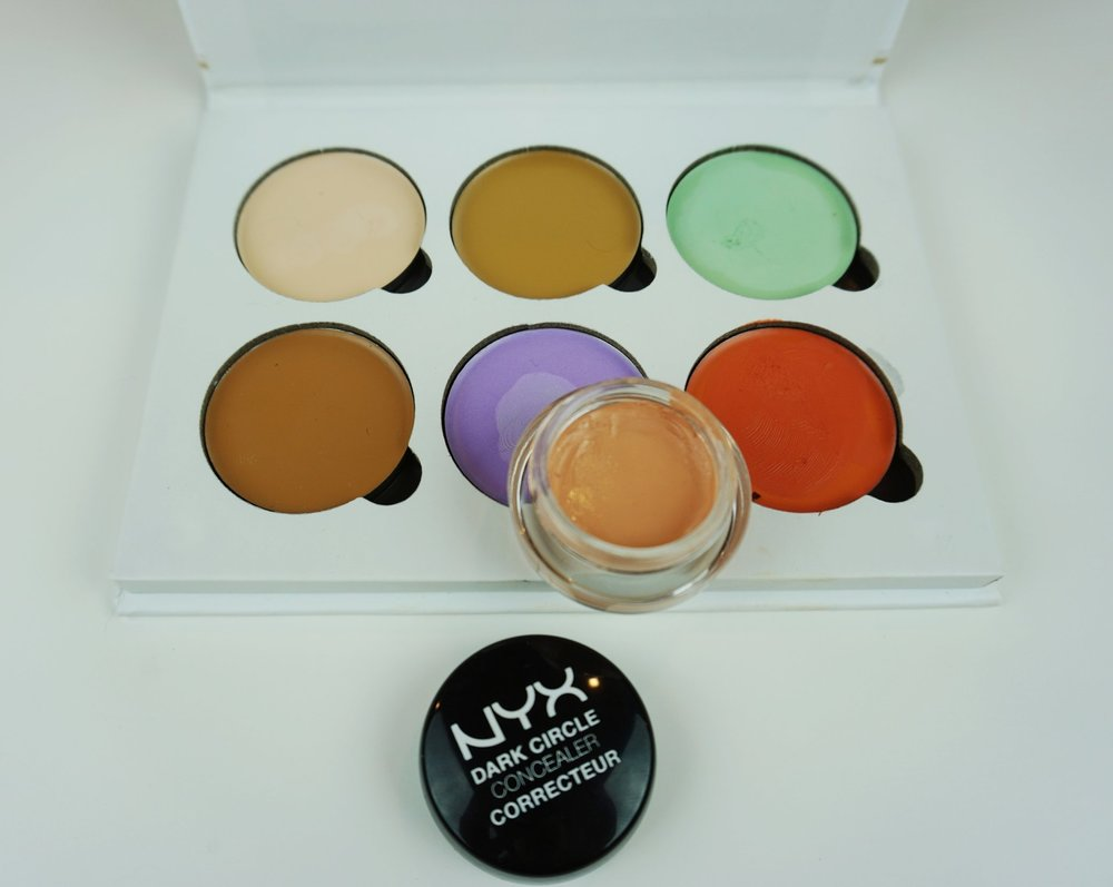 A photo of a color correcting concealer palette and NYX peach concealer.