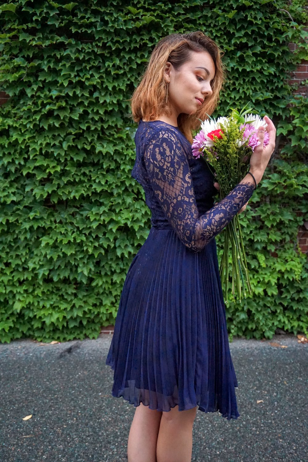 A photo of a blogger smelling the flowers, wearing a dark blue dress set.